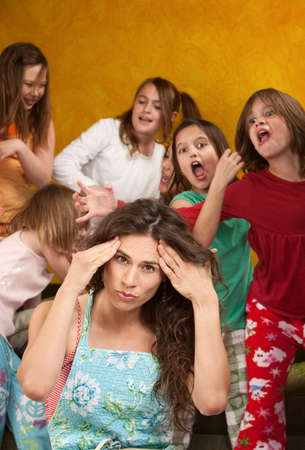 loud: Babysitter holds head with wild little girls at a sleepover