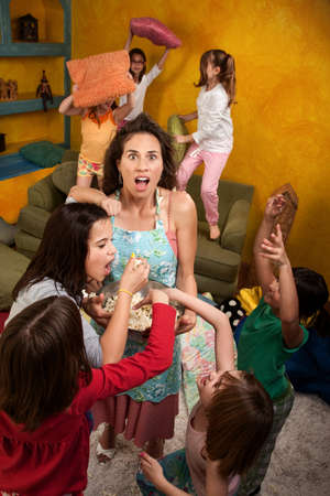 Shocked mother among wild little girls at a sleepover Banque d'images