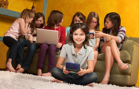 Smiling little girl playing video game on portable console with her friends