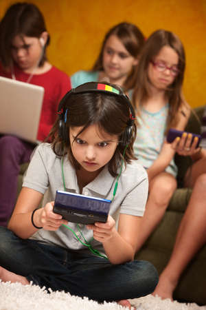 Little Caucasian girl focused on her portable gaming console photo
