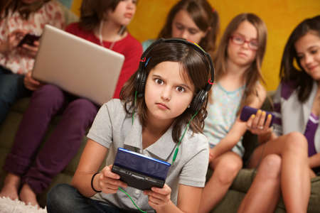 Surprised little girl with headset and portable gaming console with friends Stock Photo - 9663377