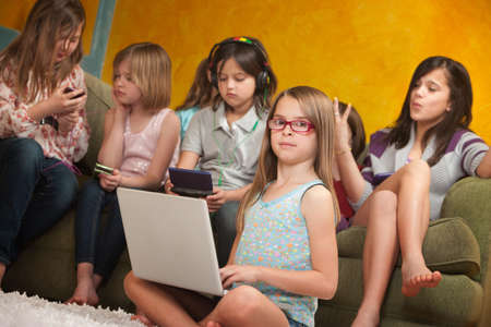 gamers: Little girl using laptop while her friends are busy playing on video game consoles