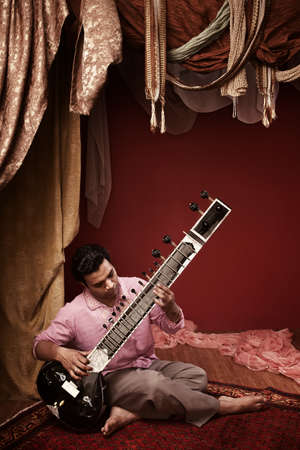 tradition: Young India man plays a sitar under ornate curtains