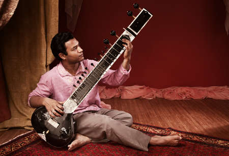 Handsome young Indian man plays a Sitar Stock Photo - 9738367