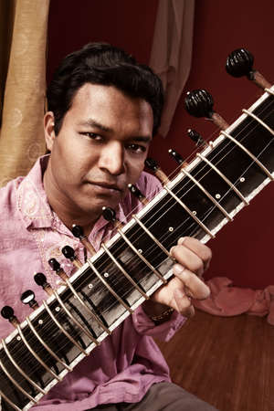 Handsome Indian man in traditional attire plays a Sitar  Stock Photo - 9738266