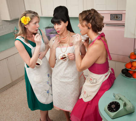 Three retro-styled women smoking cigarettes in a kitchen Фото со стока