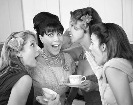 Group of four excited housewives in a kitchen share secrets photo