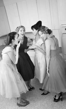 Group of four retro-styled women gossip in a kitchen  photo