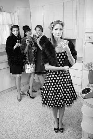 Four women smoking and drinking in a retro-style kitchen scene photo