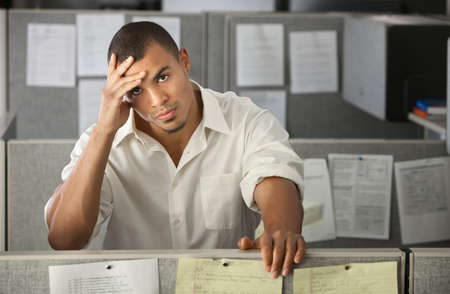 Stressed-out Latino office worker with hand on his head  photo