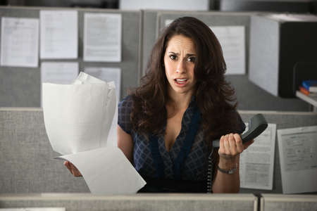 Confused female employee holds documents and a telephone photo
