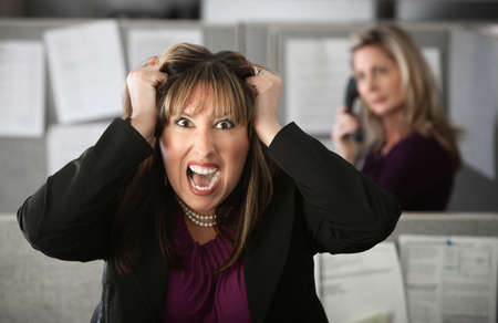 Frustrated female office worker in a cubicle pulls her hair photo