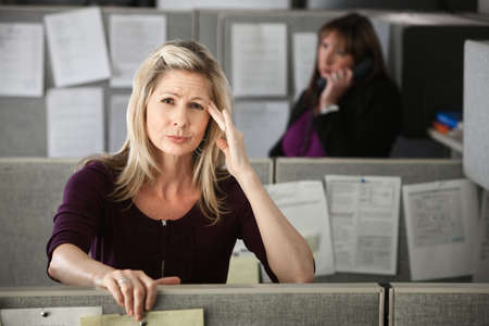 Stressed-out office worker with hand on her head