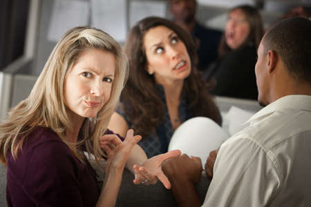 Annoyed woman with coworkers in office cubicle