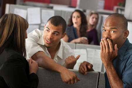 rumours: Embarrassed man with hand over mouth standing with coworkers Stock Photo