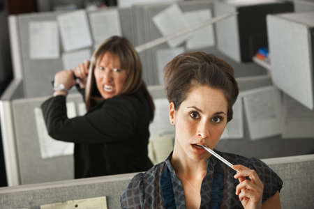 Female co-worker in deep thoughts while her colleague threatens to stab her with a Samurai sword