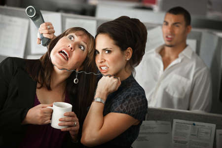 choke: Frustrated female office worker strangles her coworker with a telephone cord Stock Photo