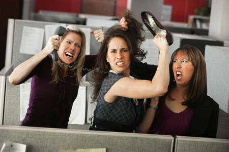 Three women office workers quarreling in cubicle