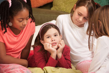 Sad little with hands on chin with friends at a sleepover photo