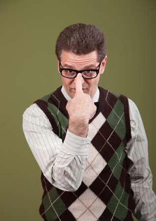 dweeb: Nerd over a green background adjusts his eyeglasses