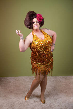 drag queen: Large woman with hand on hip over green background Stock Photo