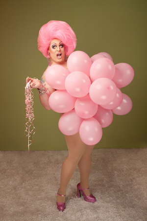 Big beautiful drag queen with pink balloons over green background