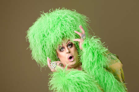 Surprised large drag queen in boa wig on green background