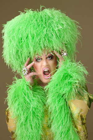 Large woman wearing heavy makeup and boa hat on green background 스톡 콘텐츠