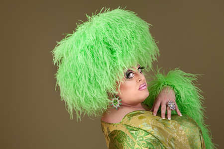 Green drag queen in matching boa hat and dress photo