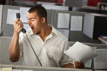 Angry Latino office worker yells on phone Stock Photo