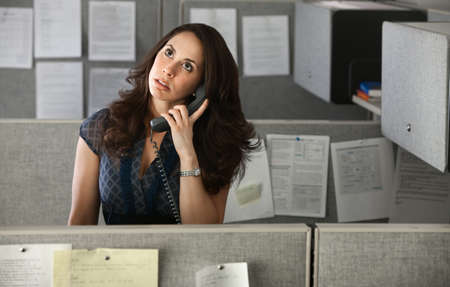 fedup: Woman office worker rolls eyes while on telephone  Stock Photo
