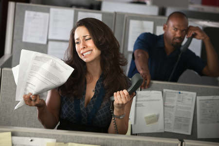 service desk: Upset woman office worker holding documents and phone  Stock Photo