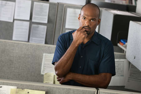 laidoff: Serious African-American man with his hand on chin stands in his office cubicle Stock Photo