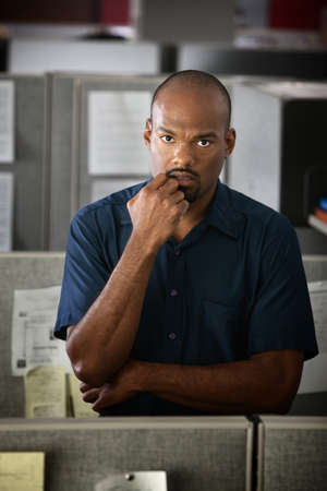 Serious African-American office worker stands in his cubicle  photo