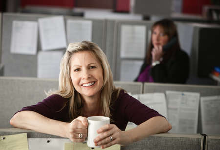 coffeetime: Woman office worker enjoys a cup of coffee at her cubicle