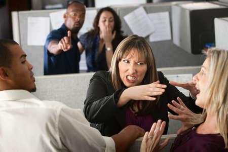 Dos compañeros de trabajo femeninos luchan en el cubículo de oficina