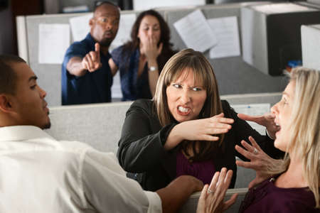violence in the workplace: Two female coworkers fight in office cubicle Stock Photo