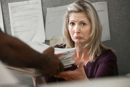 Unhappy Caucasian worker given a stack of files at a cubicle photo