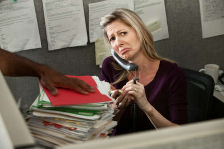 underpaid: Unhappy woman employee given a stack of files