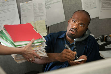 underpaid: Shocked African-American office worker on a phone call given a stack of files