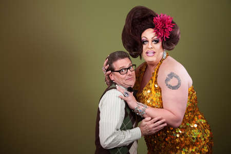 drag queen: Large woman holding a uncomfortable nerd on green background