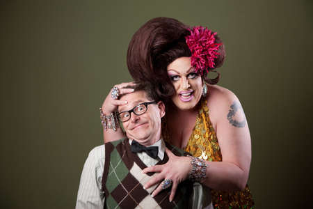 Drag queen holds a Caucasian nerd on green background  photo