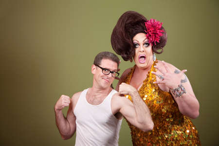 Shocked tall drag queen with short muscular man
