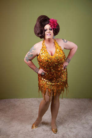 bbw: Confident drag queen with hands on hips over green background Stock Photo