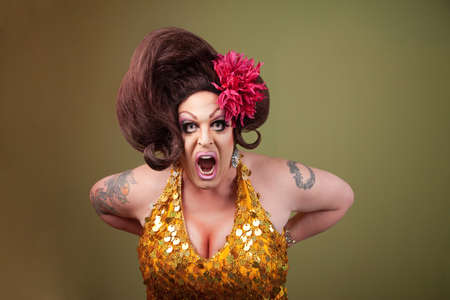 Drag queen with mouth wide open on green background photo