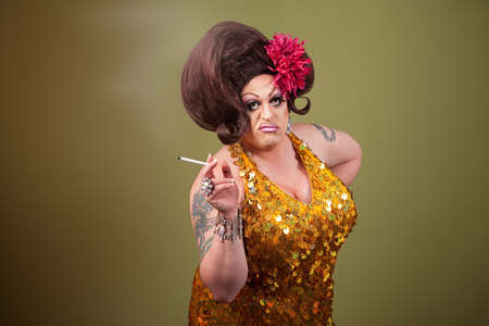 Serious drag queen smoking cigarette on green background Stock Photo