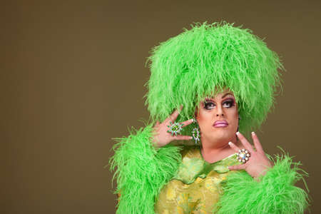 Fancy drag queen in green dress and boa wig  Stock Photo