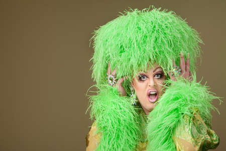 outrage: Shocked drag queen holding boa hat on green background