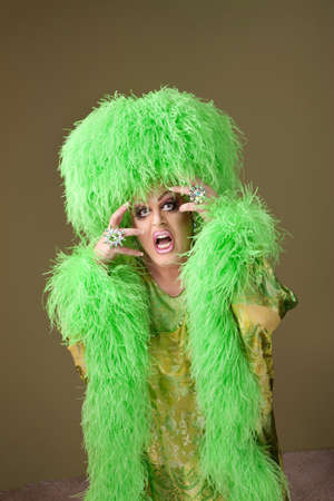 Emotional drag queen in boa and wig on green background 스톡 콘텐츠