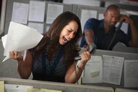 여자 직원은 그녀의 칸막이에있는 전화에 큰 소리로 외칩니다.